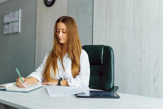 Portrait de la belle jeune femme brune souriante assise au poste de travail moderne et lumineux et en tapant sur un ordinateur portable