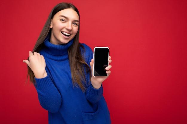 Portrait d'une belle jeune femme brune souriante portant un pull bleu décontracté isolé sur