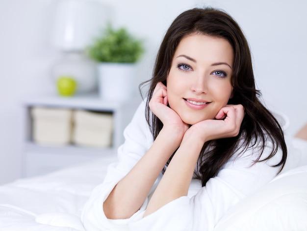 Portrait de la belle jeune femme brune avec un sourire attrayant - à l'intérieur