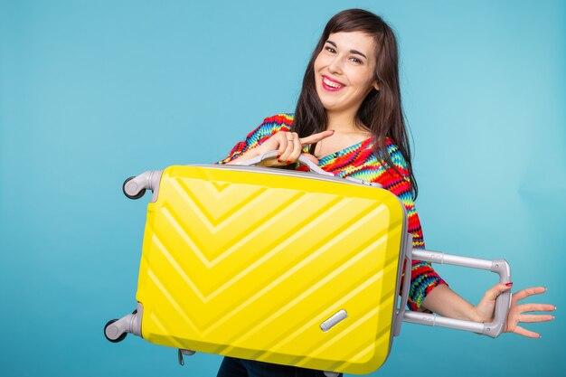 Portrait d'une belle jeune femme brune avec une valise jaune dans ses mains posant sur un mur bleu
