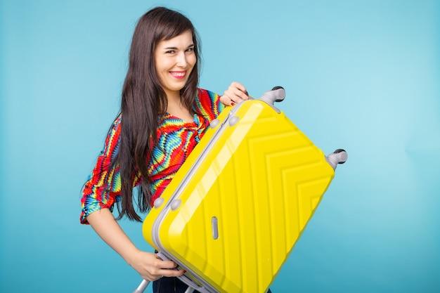 Portrait d'une belle jeune femme brune avec une valise jaune dans ses mains posant
