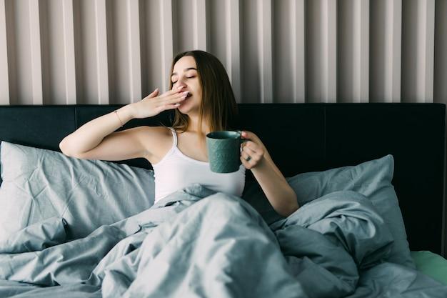 Portrait de la belle jeune femme buvant du café sur le lit