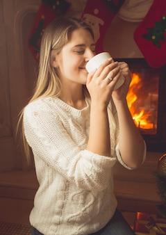 Portrait de belle jeune femme buvant du thé à la cheminée