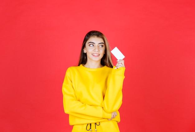 Portrait d'une belle jeune femme avec une carte de visite vierge debout et posant