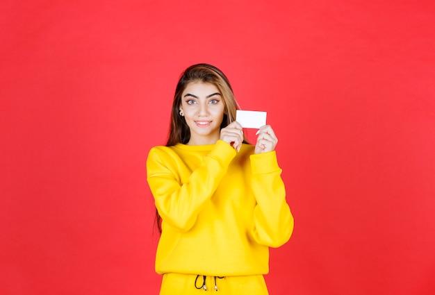 Portrait d'une belle jeune femme avec une carte de visite vierge debout
