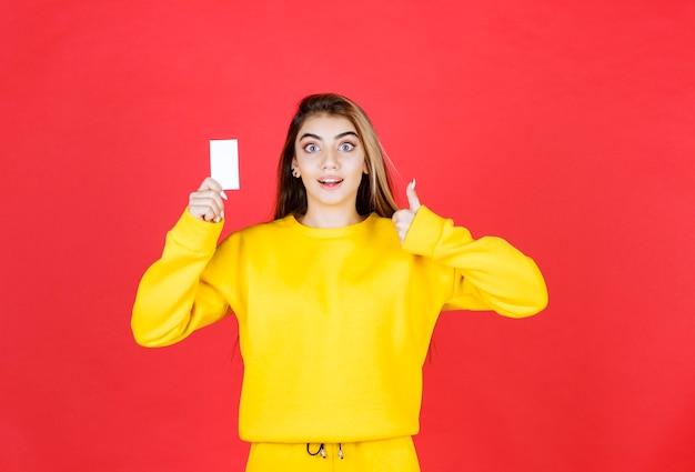 Portrait d'une belle jeune femme avec une carte de visite vierge donnant les pouces vers le haut