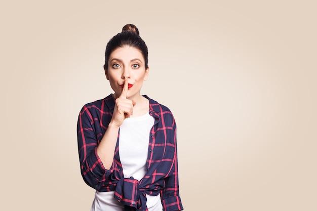 Portrait d'une belle jeune femme caucasienne avec un chignon noir tenant l'index sur les lèvres, demandant de garder le silence ou de ne dire à personne son secret, levant les sourcils, disant