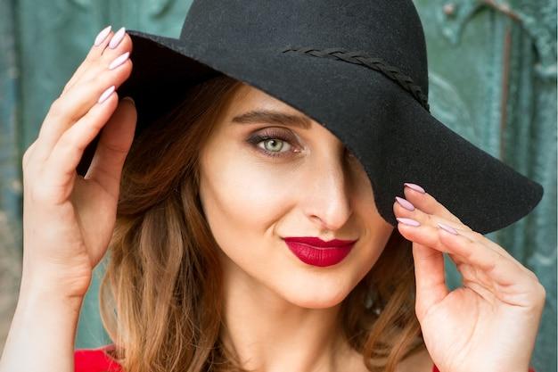 Portrait de la belle jeune femme caucasienne à la mode en robe rouge portant un chapeau noir