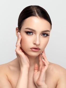Portrait de la belle jeune femme caucasienne touchant son visage. nettoyage de la peau, soins de la peau, concept de cosmétologie