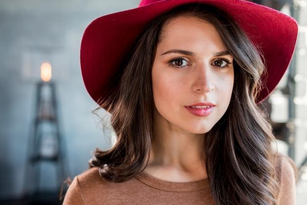 Portrait d'une belle jeune femme avec un chapeau rose sur la tête en regardant la caméra