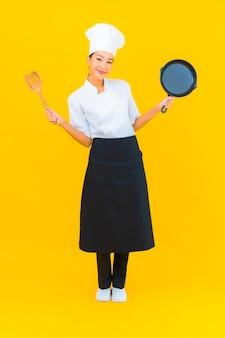 Portrait belle jeune femme chef asiatique avec pan noir sur fond isolé jaune