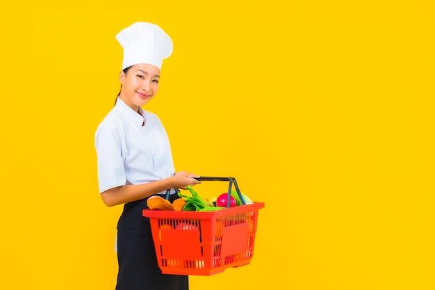Portrait belle jeune femme chef asiatique avec panier d'épicerie de supermarché sur fond isolé jaune