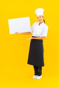 Portrait belle jeune femme chef asiatique avec panneau d'affichage vide blanc sur fond isolé jaune
