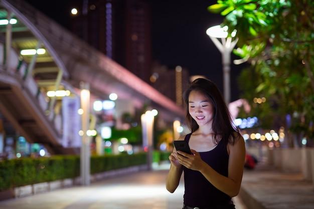 Portrait de la belle jeune femme chinoise à l'extérieur pendant la nuit