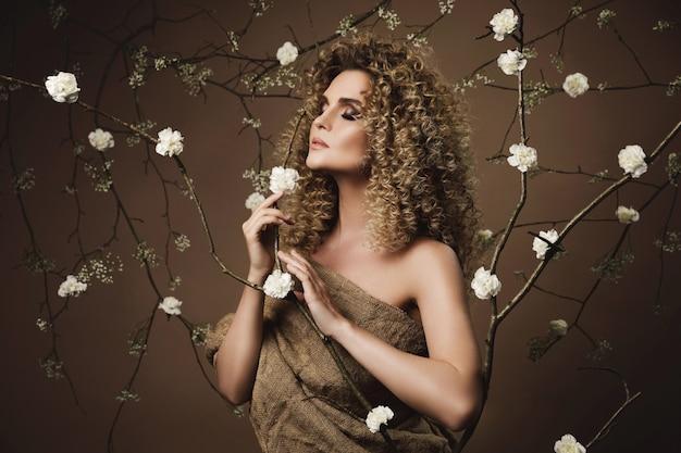Portrait de belle jeune femme avec une coiffure afro et beau maquillage avec beaucoup de fleurs blanches sur le mur