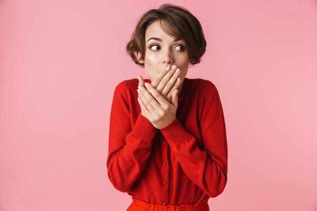 Portrait d'une belle jeune femme confus choqué portant des vêtements rouges debout isolé sur fond rose