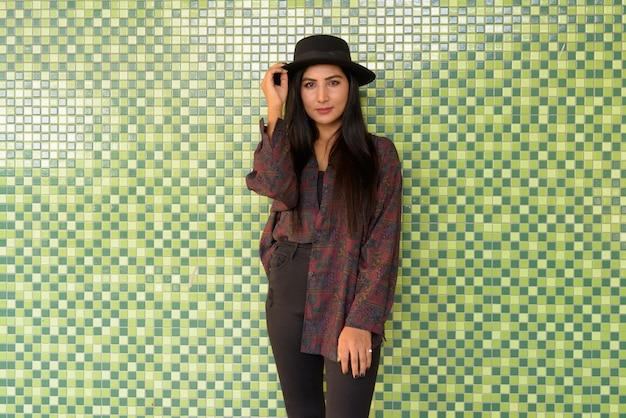 Portrait de belle jeune femme contre le mur coloré