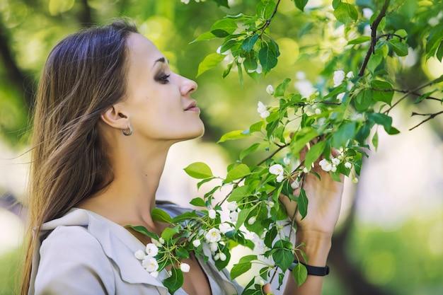Portrait de belle jeune femme à côté d'une branche d'un pommier en fleurs dans le parc à l'extérieur