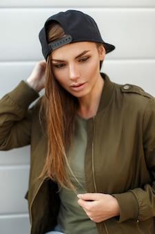 Portrait d'une belle jeune femme dans une casquette de baseball noire dans une veste verte à la mode