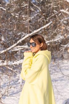 Portrait d'une belle jeune femme dans une forêt d'hiver paysage enneigé sur une journée ensoleillée, vêtue d'un gros pull jaune, avec des lunettes de soleil, profitant du soleil et de la neige