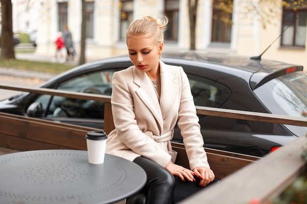 Portrait d'une belle jeune femme dans un manteau à la mode avec du café dans un café en plein air