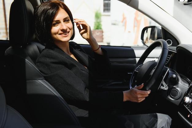 Portrait de la belle jeune femme dans la nouvelle voiture à l'aide du téléphone