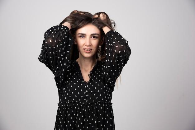 Portrait d'une belle jeune femme debout et montrant un signe ok avec les doigts.