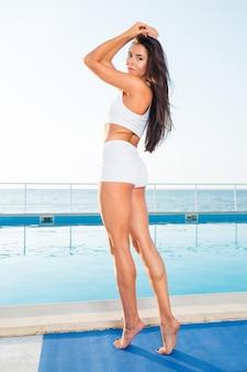 Portrait d'une belle jeune femme debout sur un tapis de yoga à l'extérieur