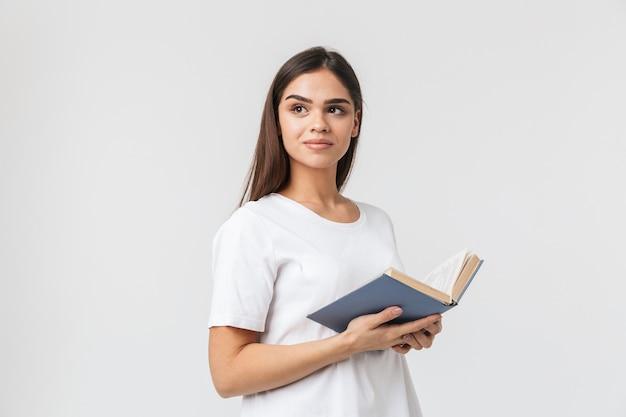 Portrait d'une belle jeune femme décontractée habillée debout isolé sur blanc, lisant un livre