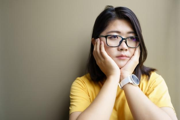 Portrait de la belle jeune femme déprimée femme assise sur le sol près de la porte à la maison.