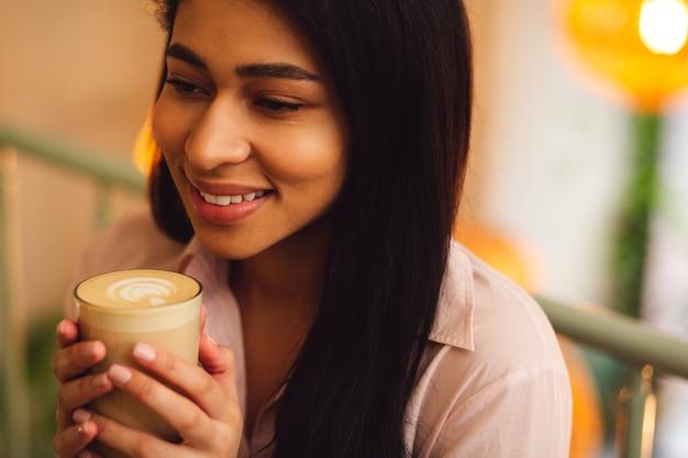 Portrait d'une belle jeune femme détendue tenant un verre de délicieux latte dans ses mains et souriant