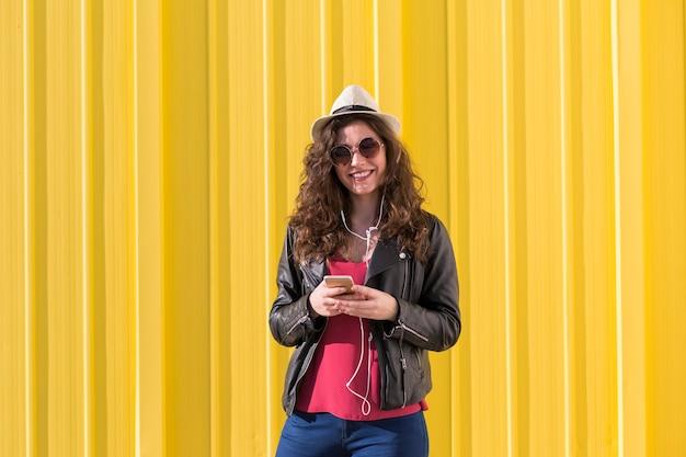Portrait d'une belle jeune femme écoutant de la musique sur son téléphone portable avec des écouteurs et s'amuser plus jaune. vêtements décontractés. porter des lunettes de soleil et un chapeau moderne.