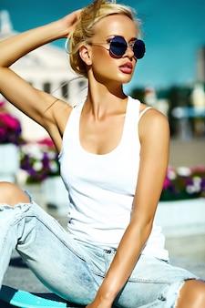 Portrait de la belle jeune femme élégante avec planche à roulettes