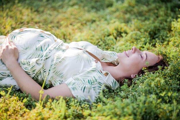 Portrait d'une belle jeune femme enceinte en robe écologique. maternité. une famille. été.