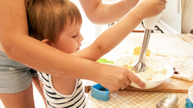 Portrait d'une belle jeune femme enseignant à son petit enfant garçon faisant des biscuits et des tartes dans la cuisine à la maison