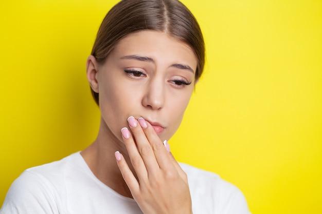 Portrait d'une belle jeune femme éprouvant un mal de dents douloureux.
