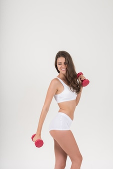 Portrait de la belle jeune femme faisant des exercices physiques avec des haltères