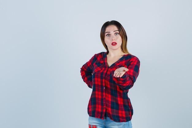 Portrait d'une belle jeune femme faisant semblant de tenir quelque chose en chemise décontractée et regardant la vue de face choquée