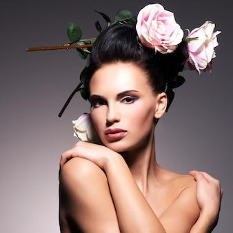 Portrait de la belle jeune femme avec des fleurs dans des poses de cheveux