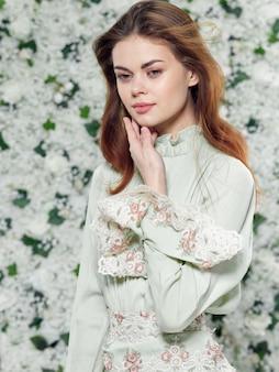 Portrait d'une belle jeune femme fond de fleurs dans une robe à fleurs