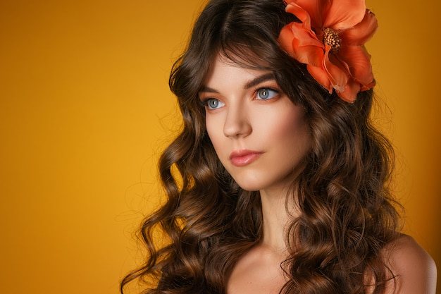 Portrait d'une belle jeune femme sur fond jaune