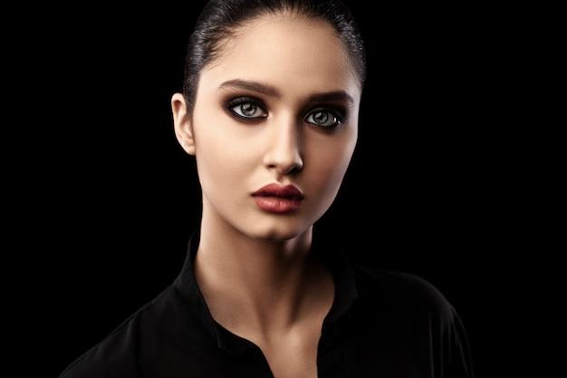Portrait de la belle jeune femme sur fond noir