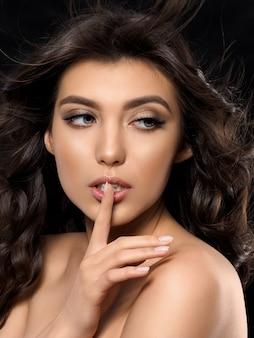 Portrait de la belle jeune femme sur fond sombre. maquillage de bronzage léger et d'été.