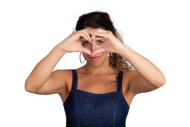 Portrait de la belle jeune femme en forme de coeur avec les mains