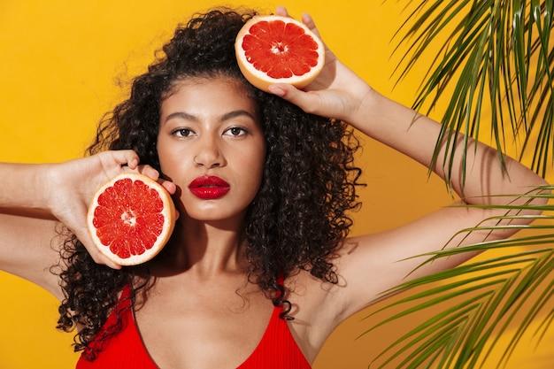 Portrait d'une belle jeune femme en forme portant un bikini debout isolée sur un mur exotique jaune, posant avec un pamplemousse coupé en deux
