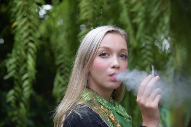 Portrait d'une belle jeune femme fumer des cigarettes. dangers de la santé.