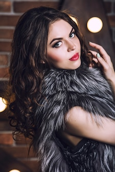 Portrait de la belle jeune femme gros plan en veste de fourrure