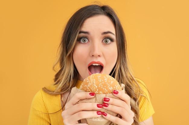 Portrait de la belle jeune femme avec hamburger sur la couleur