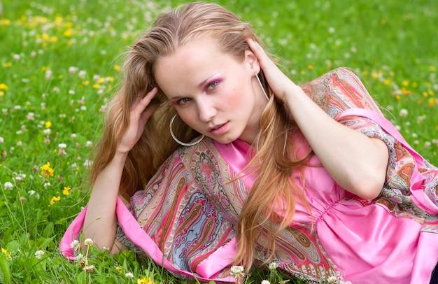 Portrait d'une belle jeune femme sur l'herbe en été