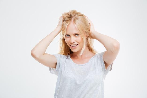 Portrait d'une belle jeune femme heureuse aux cheveux blonds sur un mur blanc